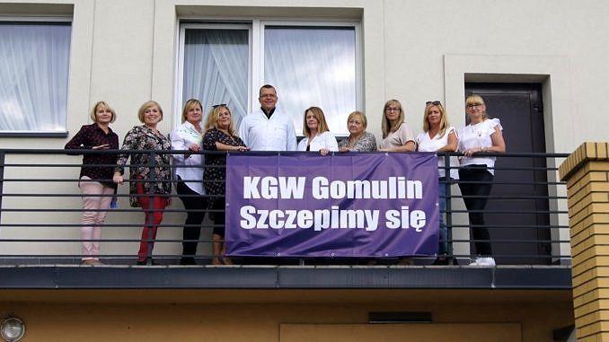 Na balkonie budynku członkinie KGW - przed nimi zawieszony baner KGW Gomulin szczepimy się