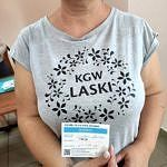 Kobieta w koszulce z napisem KGW Laski trzyma w dłoniach certyfikat potwierdzjący szczepienie