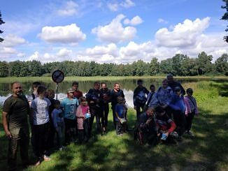 Grupa dzieci z opiekunami przy stawie w Wygodzie