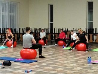 Kobiety na sali ćwiczą na czerwonych piłkach finess