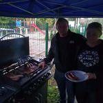 Dwoje ludzi przy grillu z kiełbaskami