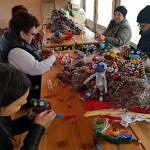 MDorośli i dzieci podczas warsztatów robienia małpek ze skarpetek