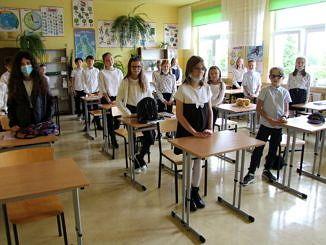 Dzieci stoją przy ławkach w klasie