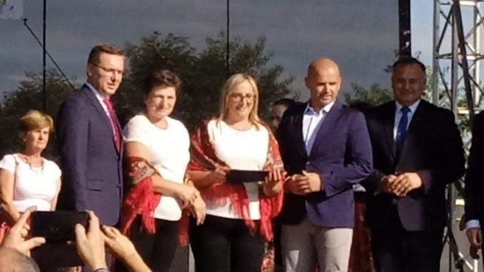 Na scenie kobiety w bialych bluzkach okryte czerwonymi ludowymi chustami i wręczający nagrodę mężczyźni