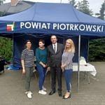 Grupa 4 osób pred namiotem z napisem powiat piotrkowski