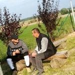 Dwaj meżczyźni siedza na drewnianycg ławkach i rozmawiają