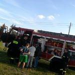 Dzieci wsiadaja do samochodu strażackiego