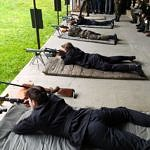 Młodzi ludzie leżą na stanowiskach strzeleckich z bronią w rękach