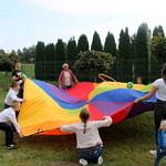 dzieci podczas zabawy tęczową płachtą w kształcie koła