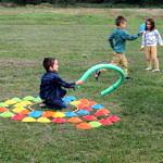 Dzieci na łące podczas zabawy kolorowymi elementami