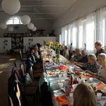 Mieszkańcy przy zastawionych stołach w sali Domu Ludowego