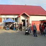 Dzieci i dorośli oglądają wóz strażacki - w tle Dom Ludowy w Piekarach z czerwonym dachem