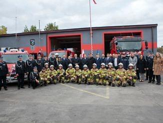 Zdjęcie grupowe - strażacy i oficjele na tle strażackich garaży