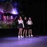 trzy dziewczynki śpiewają na scenie