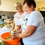 Kobiety szatkują kapustę do pomarańczowej miski