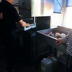 Mężczyzna wkłada naczynia do zmywarki