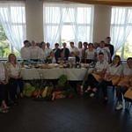 Zdjęcie grupowe osób przy suto zastawionym stole ozdobionym warzywami