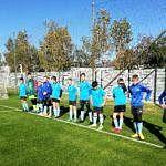 Drużyna chłopców w niebieskich strojach stoi w rzędzie przy bramce