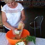 Kobieta szatkuje kapustę do pomarańczowej miski