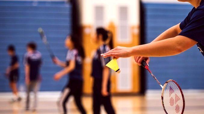 Badminton - na pierwszym planie dłoń z lotką, w tle zawodnicy