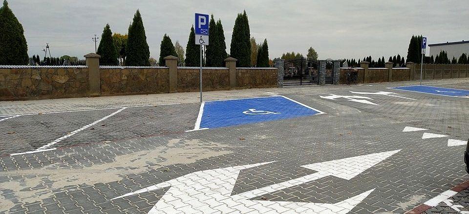 Gotowy parking z kostki betonowej i płyt ażurowych z zaznaczonymi miejscami parkingowymi i znakami poziomymi