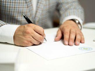 Dłonie człowieka podpisującego jakiś dokument