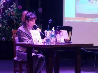 Autorka z książką na scenie siedzi przy stoliku